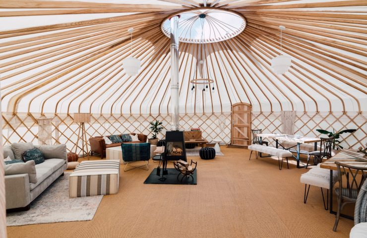 Inside our traditional handmade yurt with sofas and a log burning stove at Silverlake