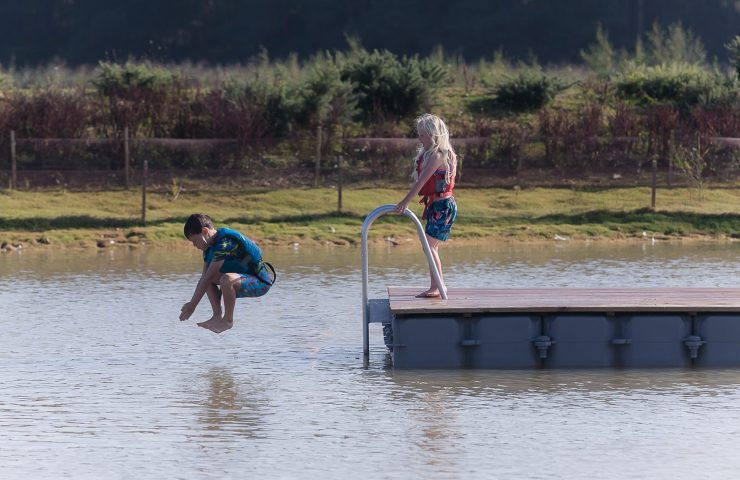 Children with life jackets jumping into the lake at Silverlake